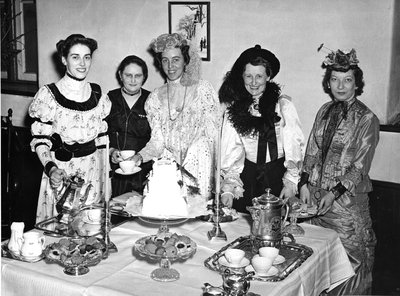 A group of women in period costumes at English style tea party