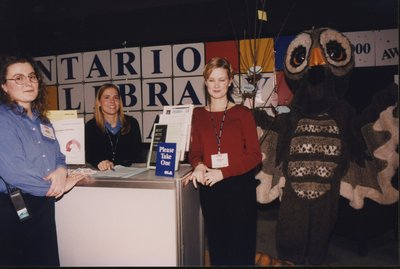 Maria Ferraro (Ripley), Katerina Podolak, and Shannon Polk with Owl Magazine's mascot at the Super Conference 2000 exhibits.