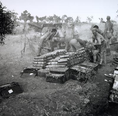 Royal Canadian Artillery personnel fire a 25-pounder at enemy positions in Nissoria, Sicily, 1943. Gunner Jim Gibb is centre right of the gun.