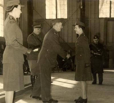 Joy Smith receiving her commission from her father, Lieutenant Colonal F.H. Dunham MC, on February 15, 1945. Looking on are Captain Carlyle (left) and Major General Potts District Officer Commanding #2 Military District (centre).