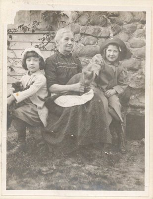 Photograph of a woman with two girls and a cat