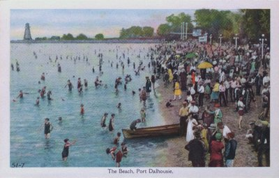 A coloured postcard of swimmers and vacationers on the shore