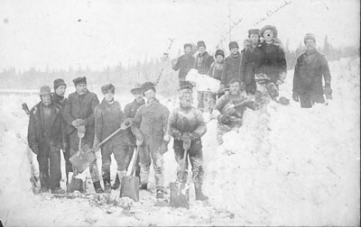 A large group of men posing with shovels in a snowbank circa 1920