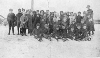 School Students Sitting in the Snow with their Teacher, circa 1920