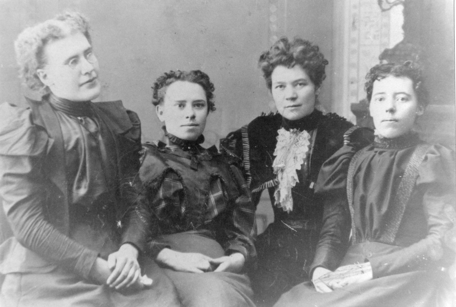 A studio portrait of four women.