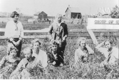 Eight young women sitting in a farm field.
