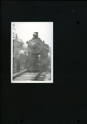 Photograph of men posing with a locomotive in the 1920s