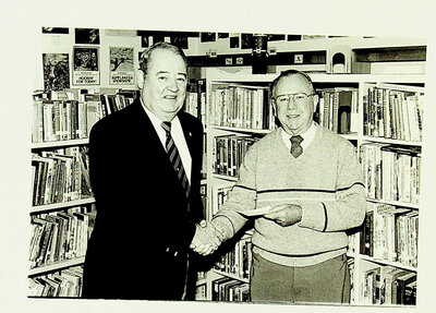 Photograph of Legion member handing over a donation to the Library, Stirling, ON