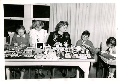 A photograph of unknown children and an adult crafting jewelry.