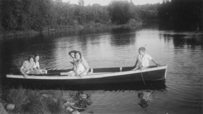 Tourists in a canoe at McAmmonds Camp, circa 1930