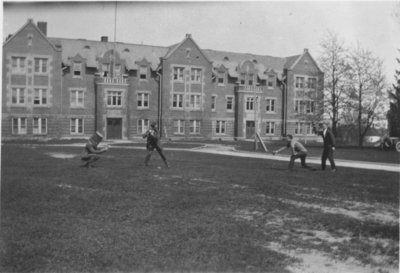 Waterloo College students playing baseball in front of Willison Hall
