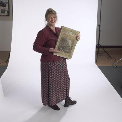Virginia McKendry holding Brantford Expositor newspaper, 2002
