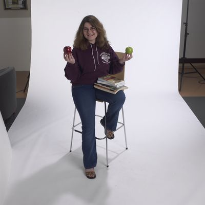 Student posing holding apples, 2002