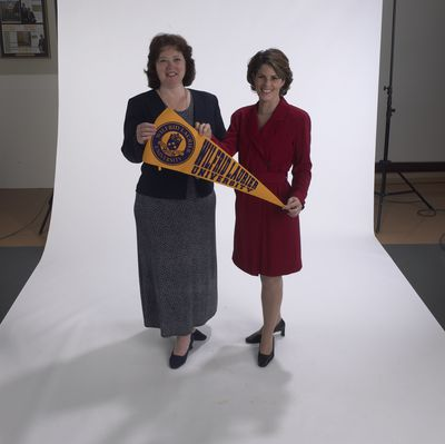 Staff members holding pennant Laurier Brantford, 2002