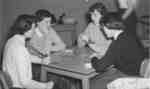Women playing a card game in girls' common room, Waterloo College