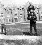 Man carrying another man on his shoulders, in front of Willison Hall