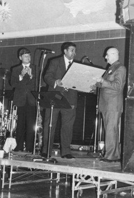 Tom Ramautarsingh presents Earle Shelley with Alumnus of the Century citation