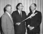 Three men holding the shaft of the Waterloo Lutheran University mace