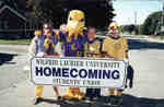Three students and the Hawk mascot at Homecoming 2001, Wilfrid Laurier University