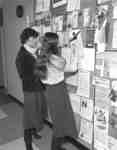 Women reading Social Work postings, Wilfrid Laurier University