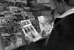 Man standing in front of magazine rack