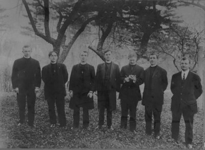 Seven clergymen standing under a tree