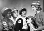 Four Waterloo Lutheran University students wearing hats and buttons