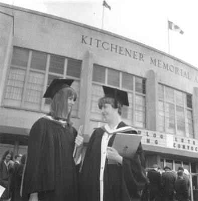 Two Waterloo Lutheran University graduates in front of the Kitchener Memorial Auditorium