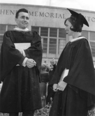 Two Waterloo Lutheran University graduates standing in front of the Kitchener Memorial Auditorium