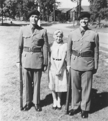 Two Canadian Officers' Training Corps cadets standing with a girl