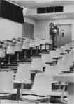 Man walking down stairs in empty lecture hall