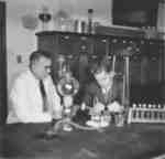 Bruce Kelley and Wilfred Myra in a science laboratory