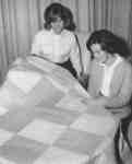 Two women admiring a quilt