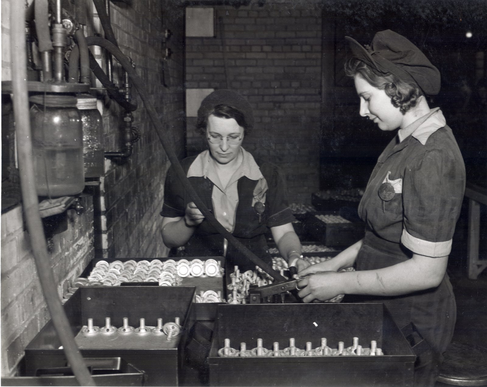 Employees Margaret MacLeod (left) and Bernice Keller (right) testing 2 inch smoke bomb adapters. Courtesy the Waterloo Public Library.