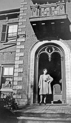 Marcella Rousseau in the doorway of the Rousseau family home (former residence of Dr. Warren), 1944