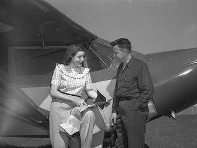 Unidentified woman and man next to Piper PA12 aircraft