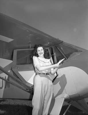 Unidentified woman standing in front of a Piper PA12 aircraft, c.1940