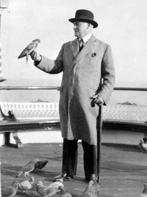 Hamar Greenwood with a bird perched on his right hand at West Pier, England, c.1940