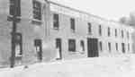Laura Pellow standing in doorway of Samuel Trees and Company (Blanket Factory), c.1915