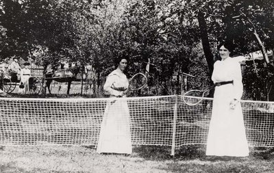 Two women playing lawn tennis