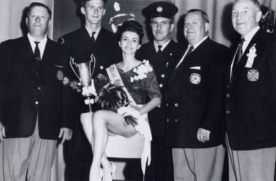 Miss Ajax Firefighter 1965 with five of the town's firefighters