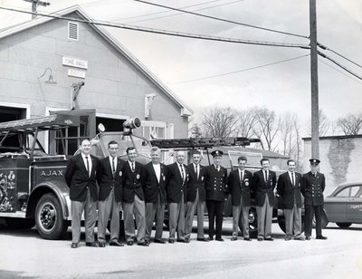 The Ajax Fire Chief and Firefighters standing in front of the fire hall