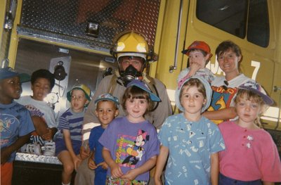 Young children standing in front of the fire truck.