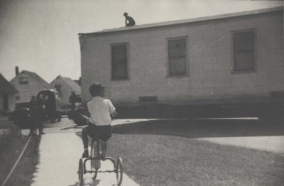 A boy on a tricycle in front of the old hospital