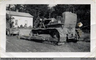 Bulldozer by an Unidentified House