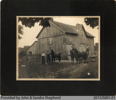Photograph of Mr. and Mrs. Fred Vivian in Front of Their Barn