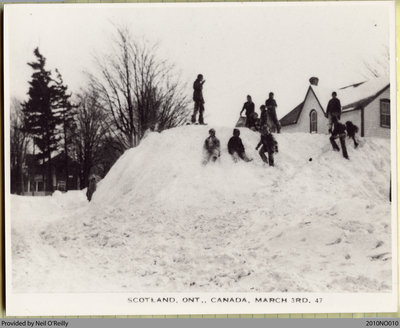 A group of children playing in a large pile of snow after a 1947 snowstorm in Scotland, Ontario