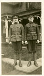 Photograph of 2 soldiers standing in front of a house