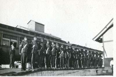 Soldiers lined up beside train with rifles in hand