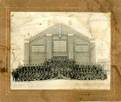 Group photograph of 6 rows of soldiers in front of a brick building